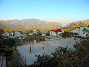Children playing soccer in Maubissi with a mountain view